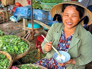 local women smiling while eating food vietnam