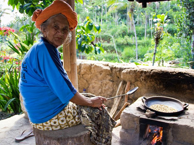 local woman roasting coffee beans in indonesia