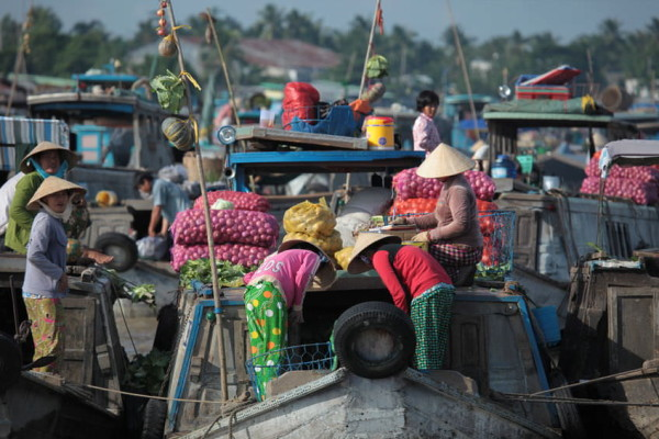 locals selling food on boat in cambodia