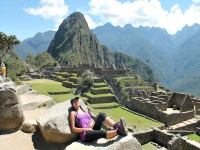 Woman lying on a rock with Machu Picchu in the background in Peru