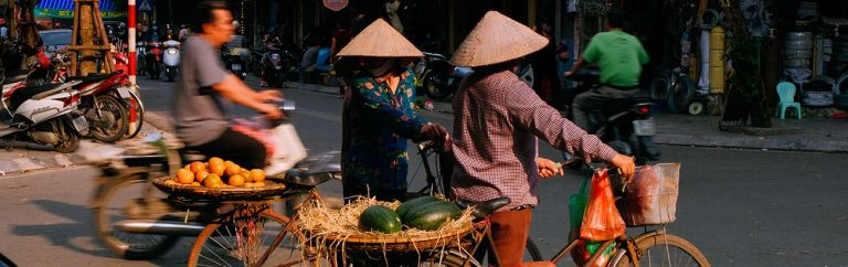 Local Vietnamese Women cycling home from the food market.