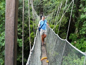 Man walking across a rope bridge in Borneo