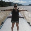 Chloe, Indonesia Travel Specialist standing with her arms spread on a narrow boat on the water in Indoensia