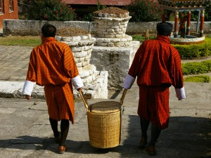 Two local men from Bhutan carrying a picnic basket between them