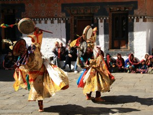 Bhutan locals dressed in traditional colourful clothing and dancing