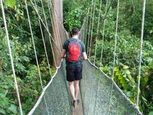 Borneo customer walking on suspended walkway in jungle