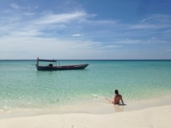 Travel Specialist sat on beach gazing out at traditional fishing boat on turquoise seas
