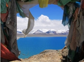 View of mountains through colorful prayer flags over namtso lake in Tibet