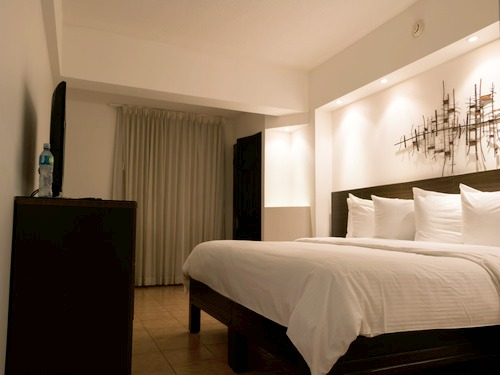 Fancy, modern bedroom with a big white double bed in Presidente accommodation