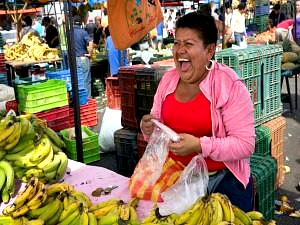Local women in San Jose in Costa Rica laughing on her banana stool in market