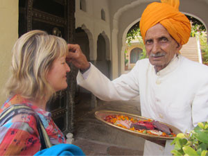 woman getting bindi spot from indian man