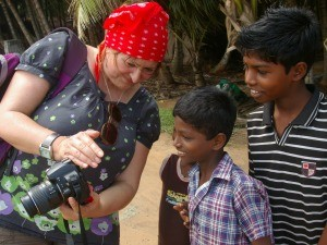 Rickshaw Travel customer, Arida, showing a group of Indian children a photo on her digital camera in India
