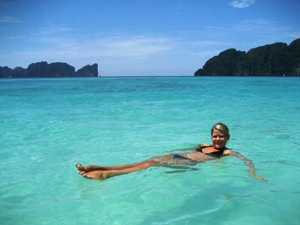 A woman floating in the sea relaxing on Langkawi Beach in Malaysia
