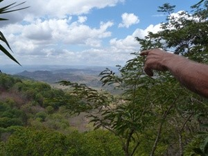 Hand pointing across luscious green valley in Nicaragua