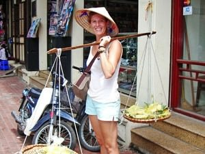 Woman with hat and food balanced on scales across her shoulders in Hanoi Vietnam