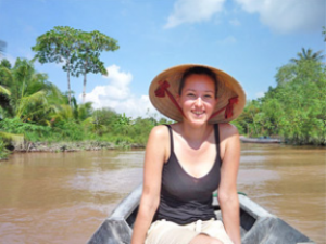 Woman sitting on a boat sailing along the Mekong River in Vietnam