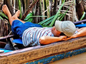 Local man lying on a boat on the Mekong in Vietnam