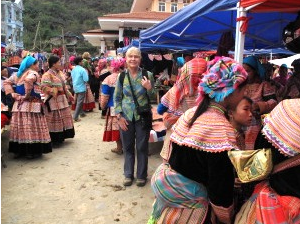 Customer on a market with women in traditional clothes