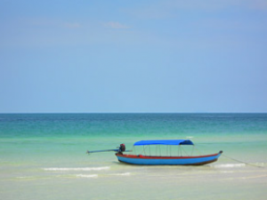 Wooden blue boat resting in the shallow waters of the Mui