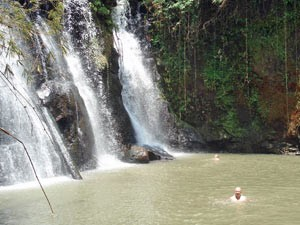Man swimming in a lagoon with flowing waterfalls in Banlung, Cambodia