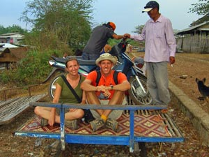 Couple sitting on a bamboo train smiling in Battambang Cambodia
