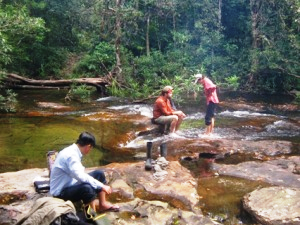 People resting in the rock pools of a river in the Cardamom Mountains in Cambodia