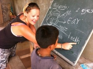 Smiling woman teaching children by a blackboard