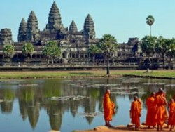 View of the Angkor Wat temples from across the water with orange-robed monks standing at the waters edge