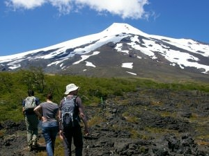 People hiking past snow-capped volcano