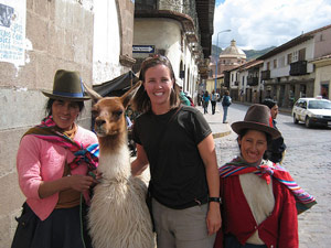 Local Peruvians and a tourist standing with a llama