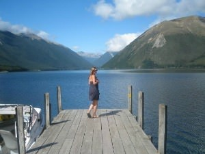 woman standing on pier looking over lake