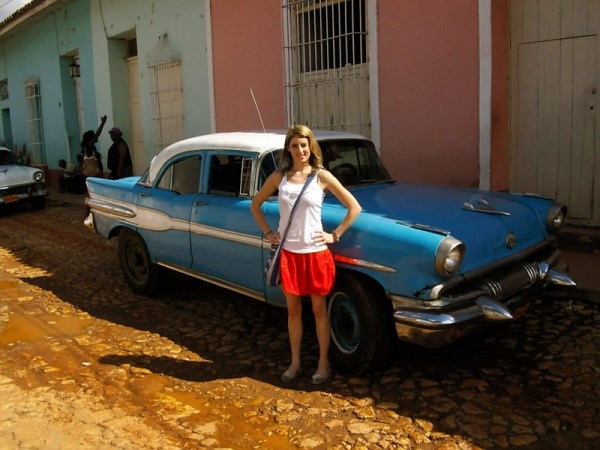 Woman standing by classic car in Cuba