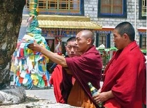 Tibet monks touching prayer flags
