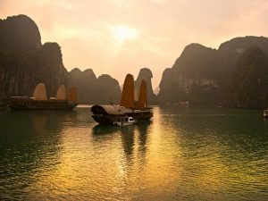 junk boat in bai tu long bay at sunset