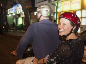 Woman on the back of a vespa riding through Ho Chi Minh City in Vietnam