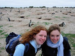 Two women travellers with penguins in the background in Argentina