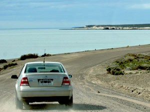 car driving down coastal road, argentina