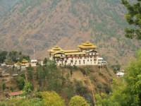 View across a luscious green landscape with a Trashigang Dzong in the distance