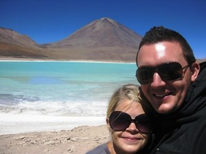 Couple smiling in front of salt flats in Bolivia