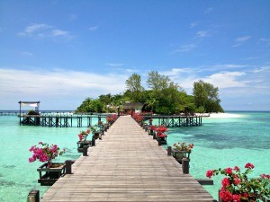 View of a jetty surrounded by flowers and aqua blue waters on Lankayan Island, Borneo