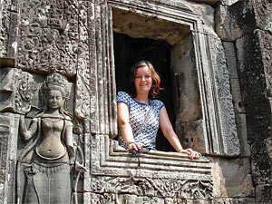 Woman standing at a window in Angkor Wat temple in Cambodia