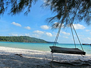 Cambodian island beach with swing bench overlooking turquoise sea