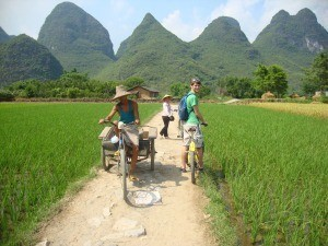 Man cycling past karst mountains