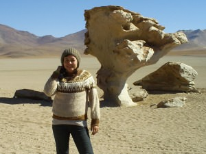Woman in jumper and hat standing in desert near big rock