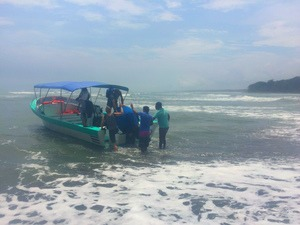 Rickshaw staff being accompanied onto transport boat by the locals in Costa Rica