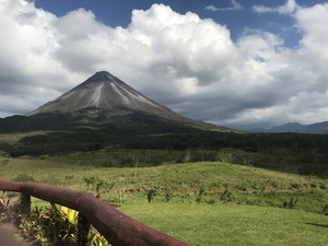 La Fortuna Arenal Volcano in the background of green shadowed fields on excursion
