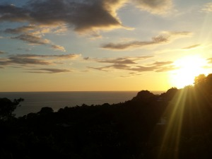 Orange sun setting behind the shadowed hills looking out over the beach at Manuel Antonio