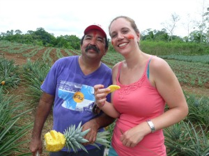 Farmer and visitor on a pineapple farm in Sarapiqui, Costa Rica holding a pineapple.