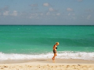 Girl walking along sandy beach, Cuba