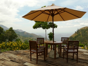 Seating area on hotel terrace overlooking lush valley